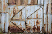 Closed old rusty iron gate sash in a corrugated iron wall. Abandoned industrial building. Grunge.