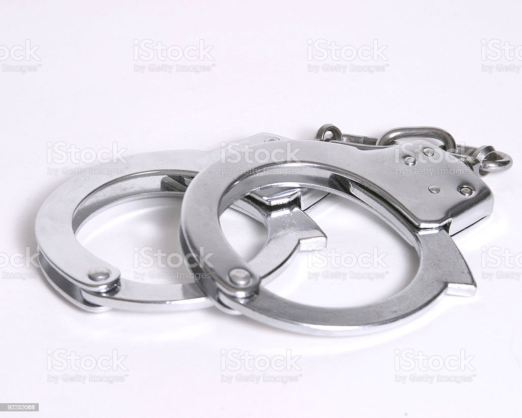 Closed pair of handcuffs against a white background royalty-free stock photo