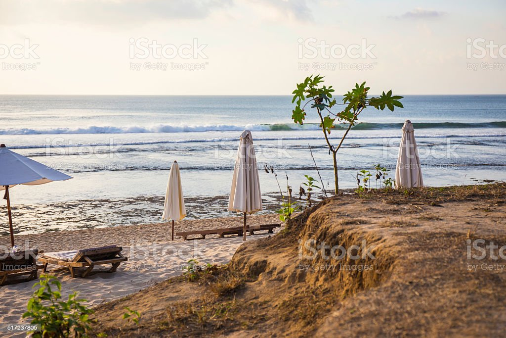 Closed parasols on the beach at sunset stock photo