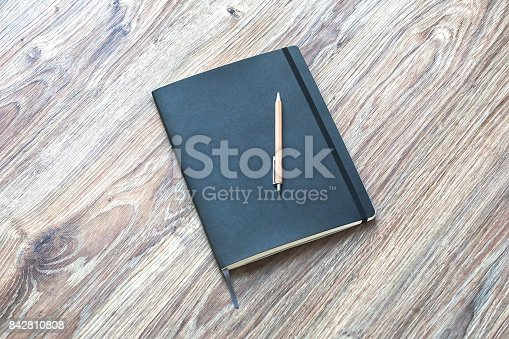 istock Closed planner with pen is on a wooden desk. 842810808
