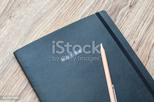 istock Closed planner with pen is on a wooden desk. 842810992