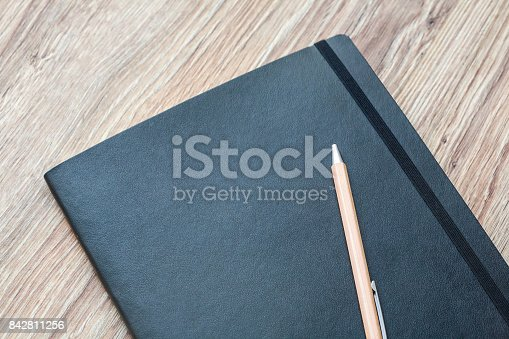 istock Closed planner with pen is on a wooden desk. 842811256
