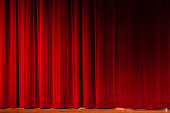 Closed red velvet stage drapes, lit by footlights, await the performer, speaker, or event. The floor of the stage is just visible. Also useful as graduated red, textured background.