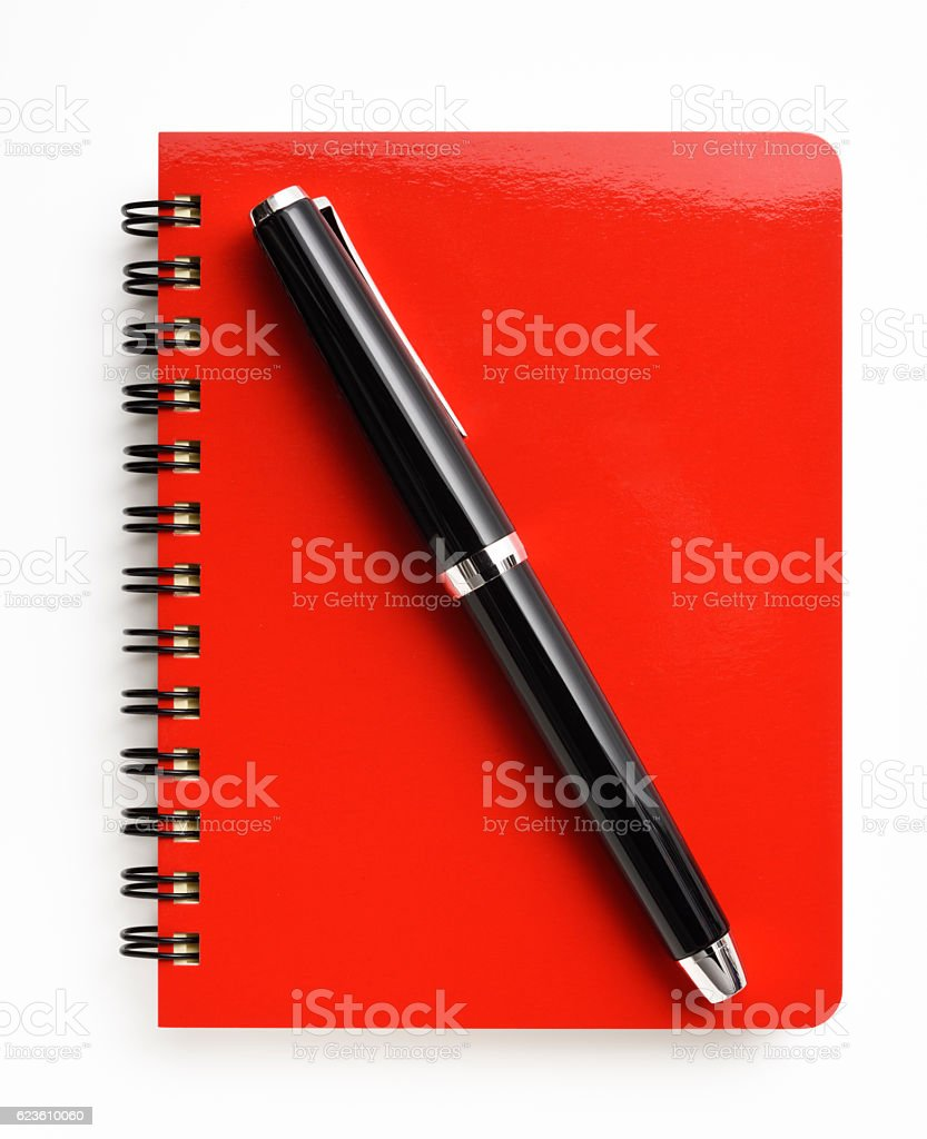 Overhead shot of opened spiral notebook with fountain pen, isolated...