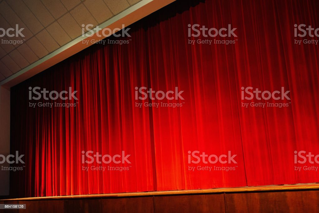 Closed red velvet stage curtains, lit by footlights stock photo