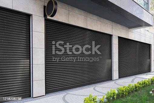 istock Closed Shops black metal roller shutter door. 1218208738