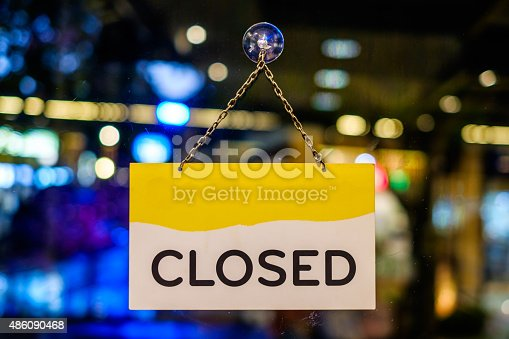 istock Closed sign hanging in a shop window 486090468
