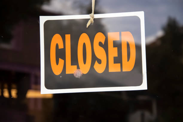 closed sign hanging in business window by a string - crooked with glob of glue also attaching it to window - some abstract reflections - closed stock photos and pictures