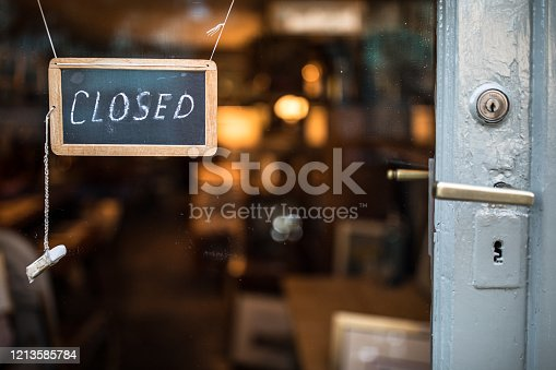 Closed - sign hanging on glass door of a shop in a city