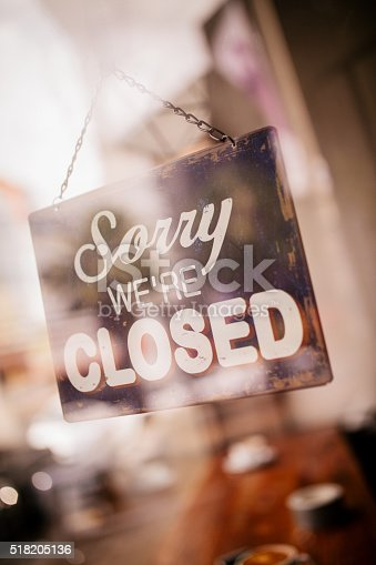 Closed Sign on glass front door of coffee shop with reflection of street in glass