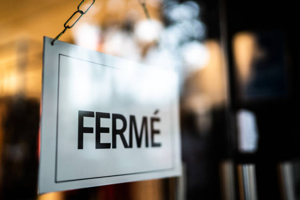 Closed sign (fermé) seen through glass by at store stock photo