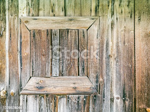 1124475954 istock photo closed small window frame on weathered wooden barn wall. closeup view 1229528044