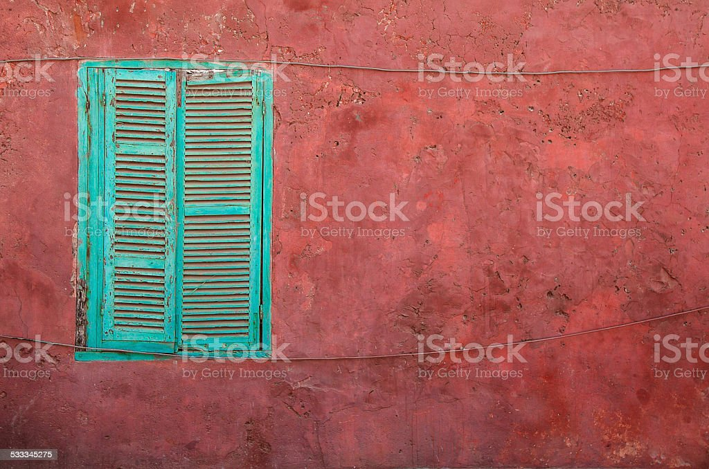 Closed turquoise shutters and a dark pink wall stock photo