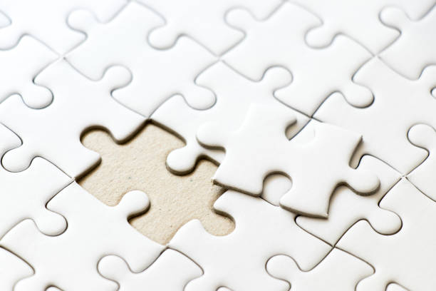 Closed up background of white plain jigsaw wait missing piece to match or fulfill Closed up background of white plain jigsaw wait missing piece to match or fulfill trabajo en equipo stock pictures, royalty-free photos & images