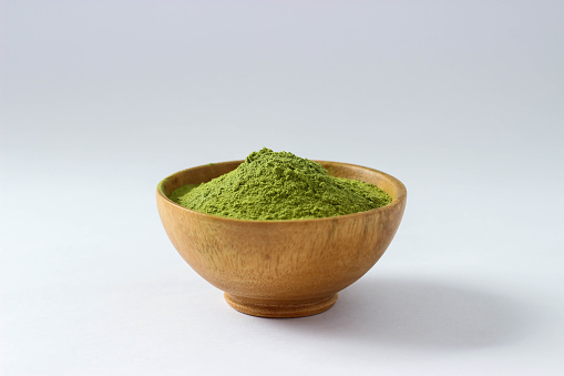 Closed up isolate extract Green Tea powder in wood bowl.