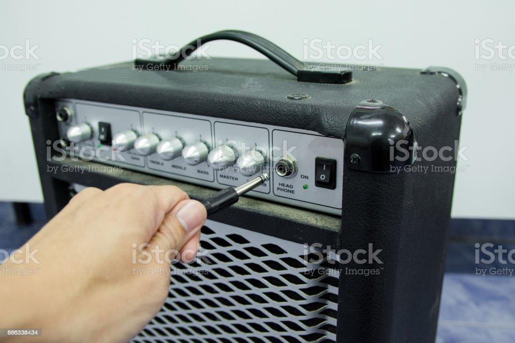 閉合的人手拿著傑克音訊外掛程式對吉他放大器, 選定的焦點圖像檔