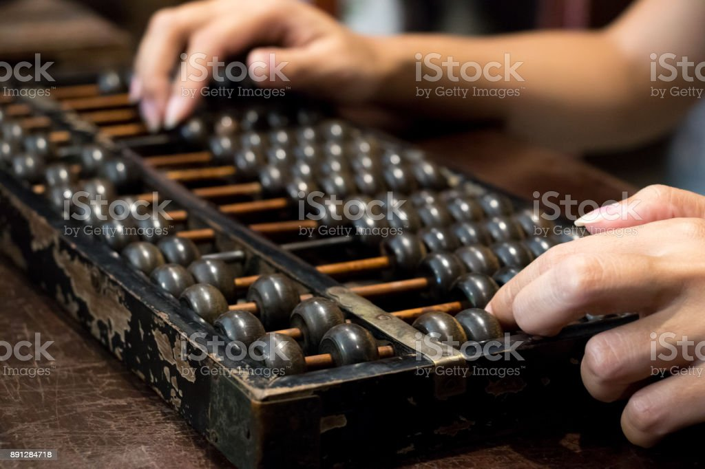Closed up of business woman hand that calculate with wood abacus (Traditional chinese calculator) stock photo