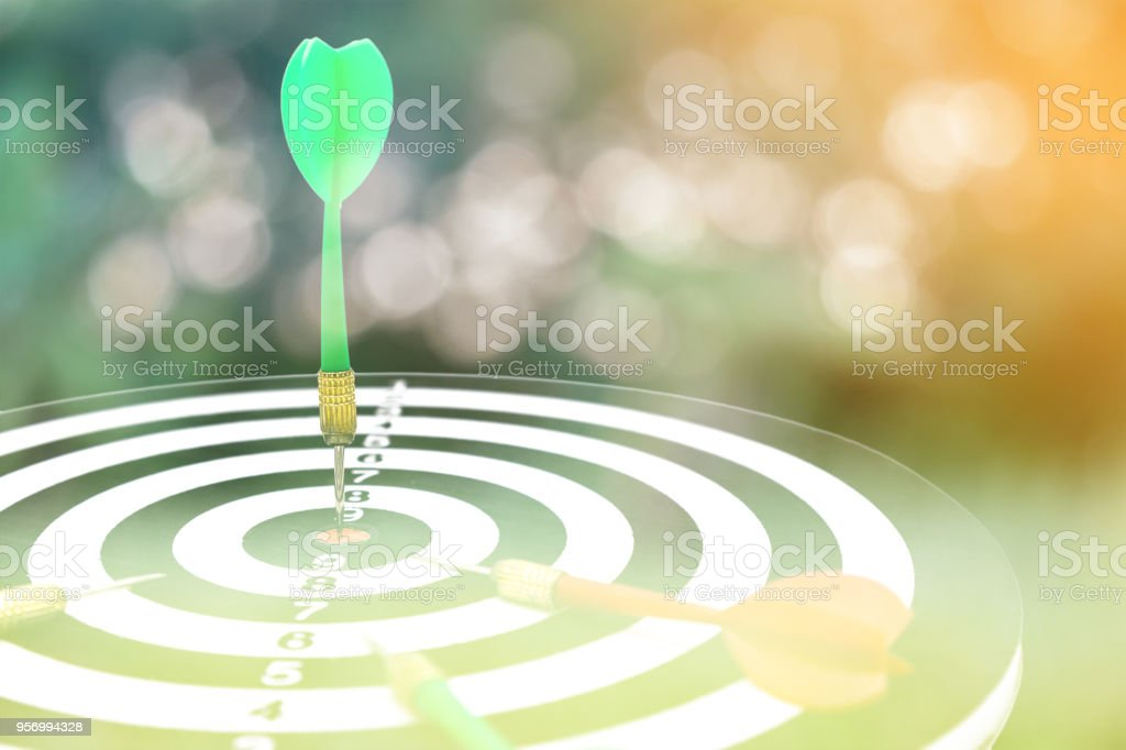 Closed up of dartboard and arrows isolated on green bokeh background, sport and business goal concept. stock photo
