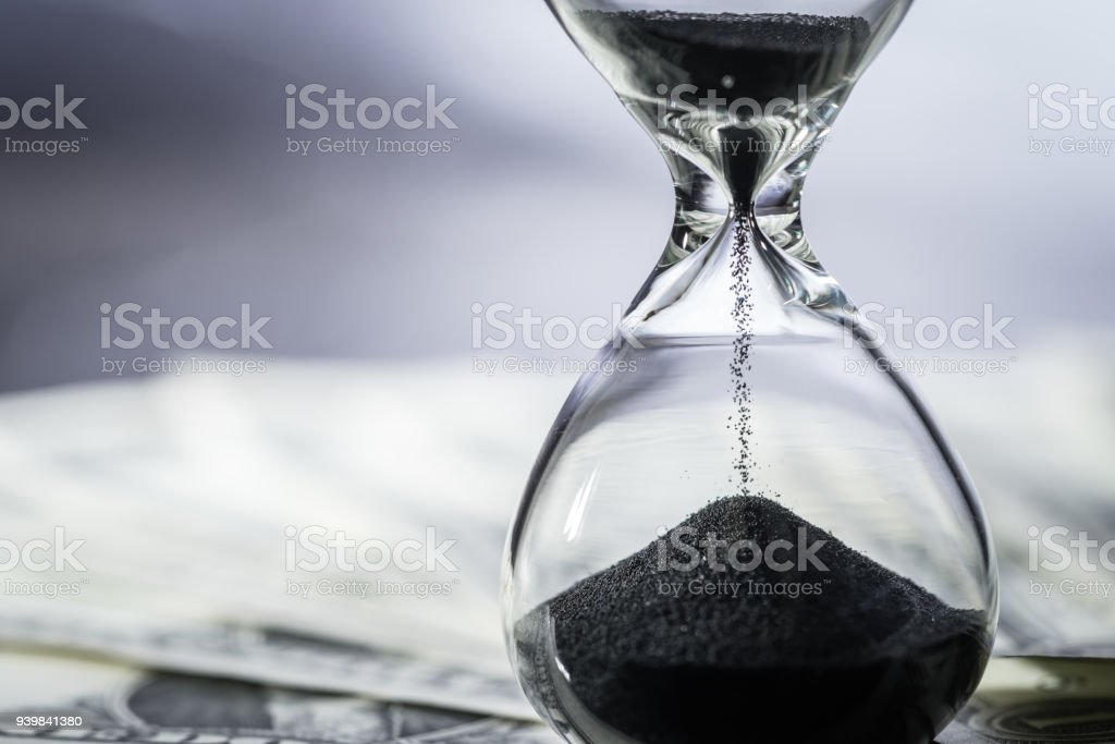 Closed up of sand falling in sandglass or hourglass on US Dollar bills as time running, long term investment or financial deadline concept stock photo