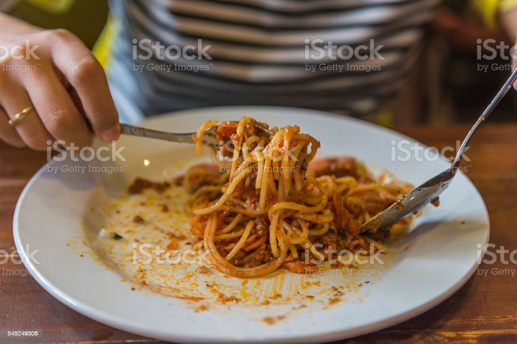 Closed up of woman hand eating spaghetti with fork stock photo