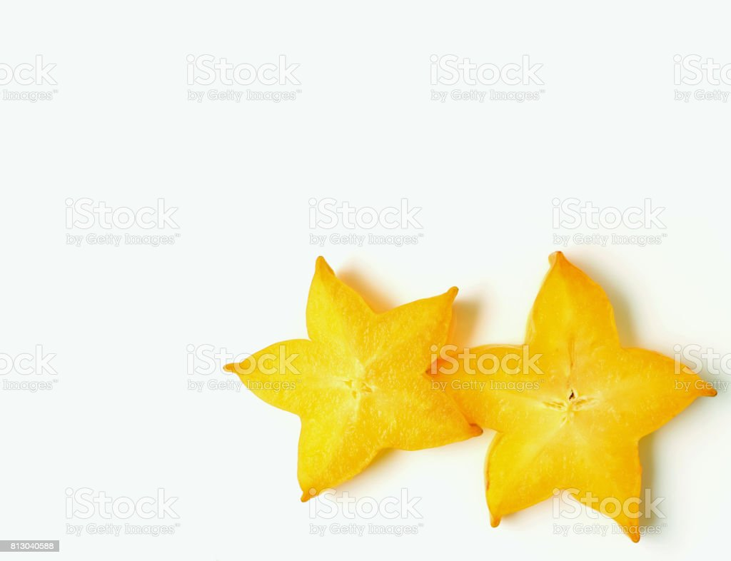 Closed up pair of vibrant yellow sliced ripe Star Fruits on white background, with free space for design and text stock photo