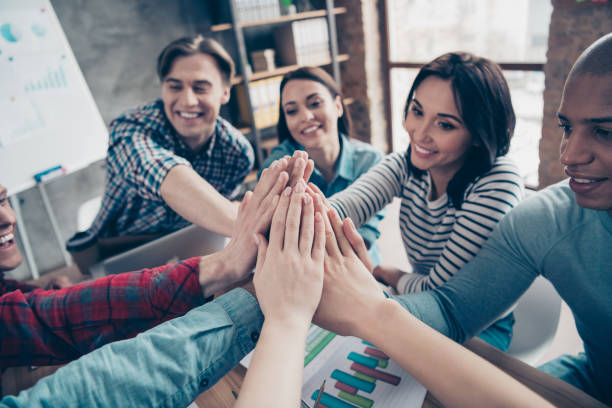 Closed up photo of colleagues coworkers touching palms guys feeling cheerful doing coaching exercises dressed in casual shirts in cozy boardroom office stock photo