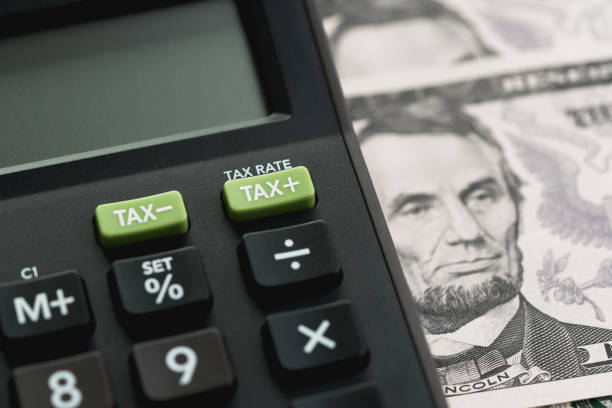 Closed up shot of TAX minus / plus buttons with text TAX RATE on calculator with background of US Dollar banknotes, United States government tax calculation stock photo
