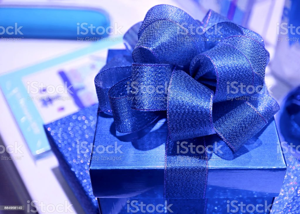 Closed up square shaped vibrant blue gift box with gritter blue...