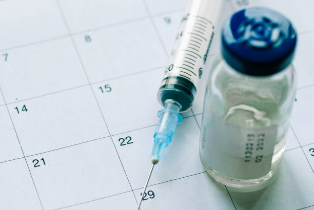 Closed vial with vaccine and empty syringe stock photo