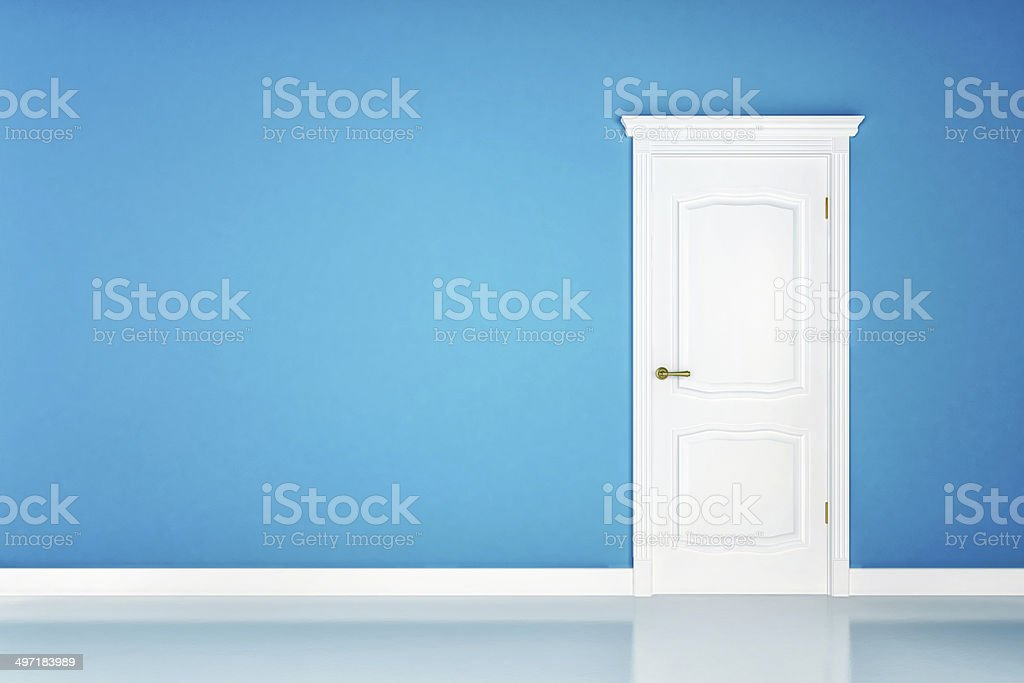 Closed white door on blue wall stock photo