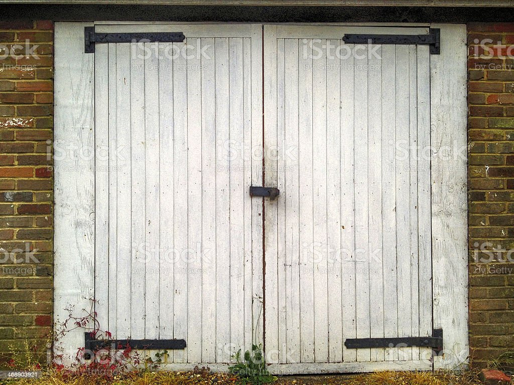 Closed white double barn doors set in a brick wall stock photo