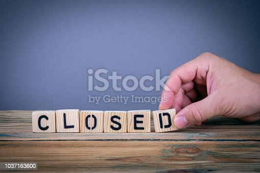 1018285596 istock photo closed, wooden letters on the office desk 1037163600