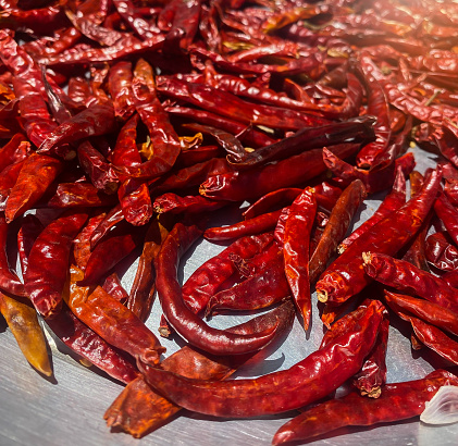 closed-up Several pieces of dried red chilies were arranged in a messy place and illuminated by light.