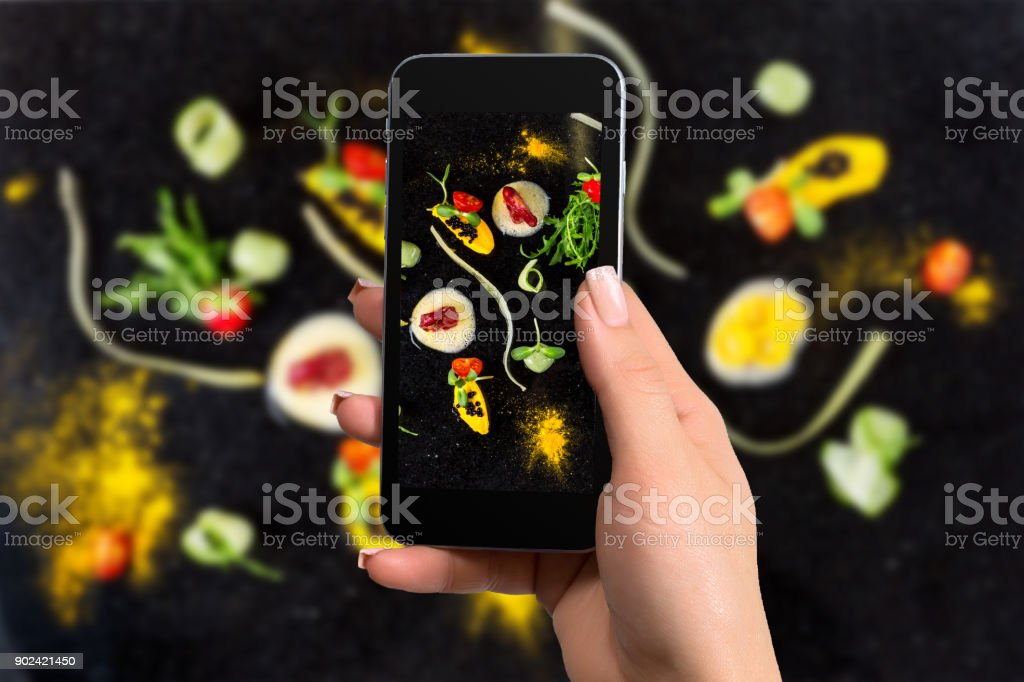 Closely image of female hands holding mobile phone with photo camera mode on the screen abstract gastronomy vanguard concept molecular cuisine stock photo