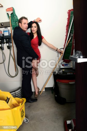 Business couple caught in surprise kissing in a janitor's closet.