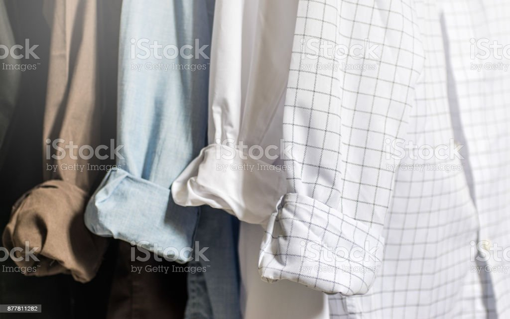 Closet wardrobe interior, showing men's dress shirts with folded and cuffed cuffs, white, blue, brown and black shirts, with light tones and soft focus stock photo