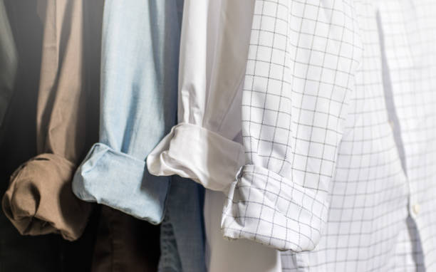 closet wardrobe interior, showing men's dress shirts with folded and cuffed cuffs, white, blue, brown and black shirts, with light tones and soft focus - menswear stock photos and pictures