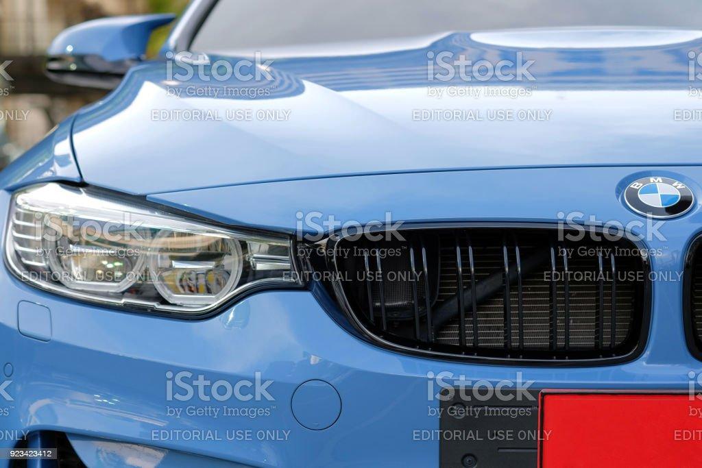 Close-up a headlight of BMW M4 sport blue car