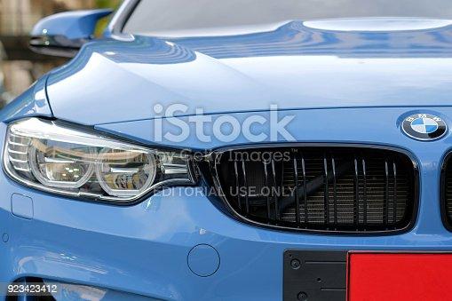istock Close-up a headlight of BMW M4 sport blue car 923423412