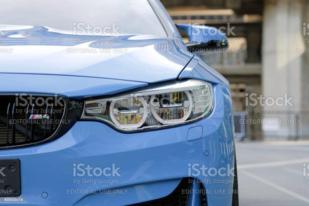 Close-up a headlight of BMW M4 sport blue car stock photo