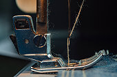 Close-up. A sewing machine sews Denim. Clothes for workers. Macro shooting. Sewing Still Life.