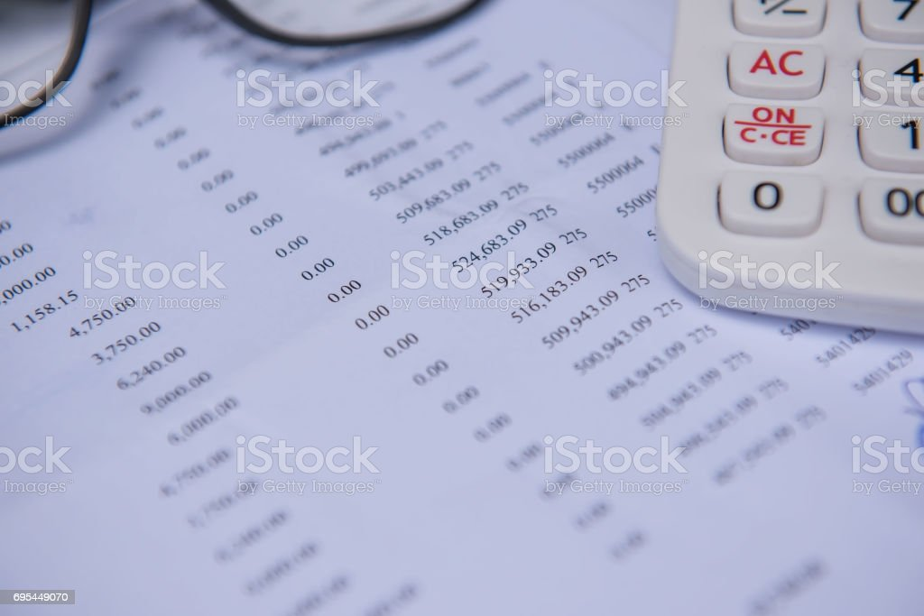 closeup accounts number on a printed paper ,Calculator and glasses. stock photo