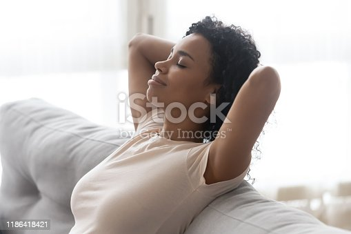 Close up african serene woman closed eyes putting hands behind head resting leaned on comfortable couch enjoy fresh cool air at hot summer day in living room at home, no stress lazy weekend concept