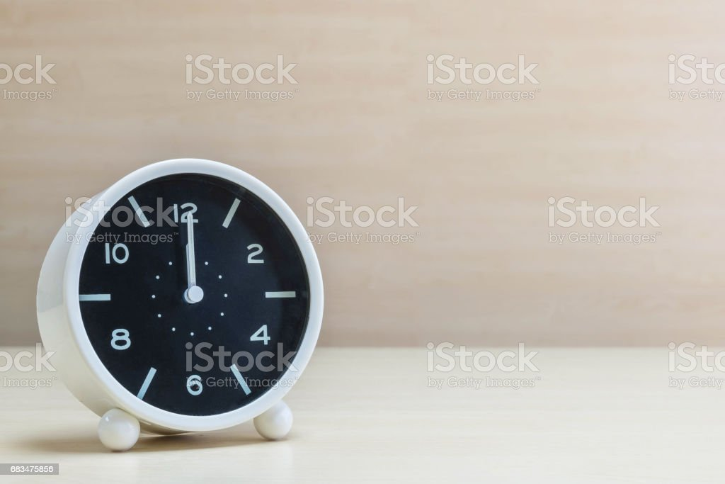 Closeup alarm clock for decorate in 12 o'clock on brown wood desk and wall textured background with copy space stock photo