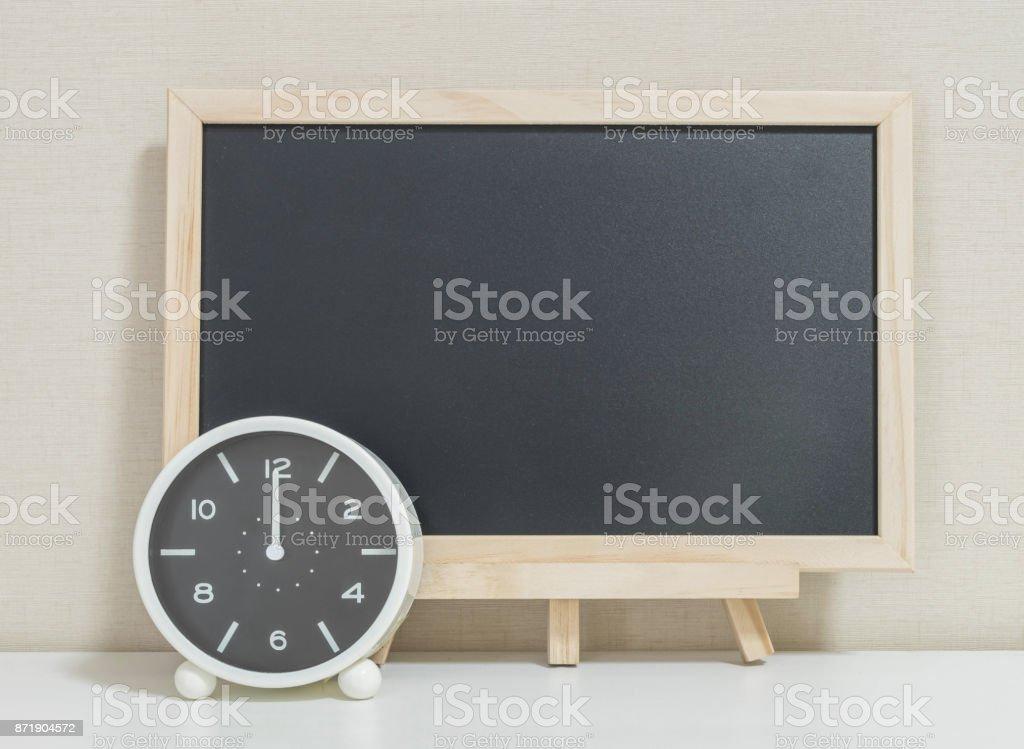 Closeup réveil pour décorer avec une planche de bois noir sur