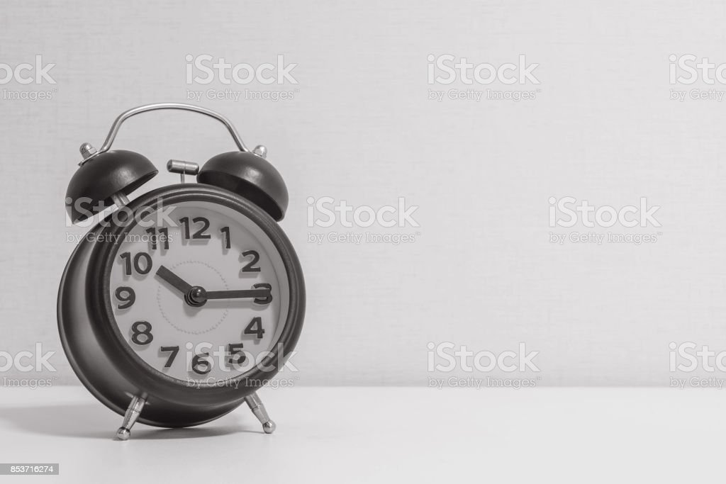Closeup alarm clock for decorate show a quarter past ten o'clock or 10:15 a.m.on white wood desk and cream wallpaper textured background in black and white tone with copy space stock photo
