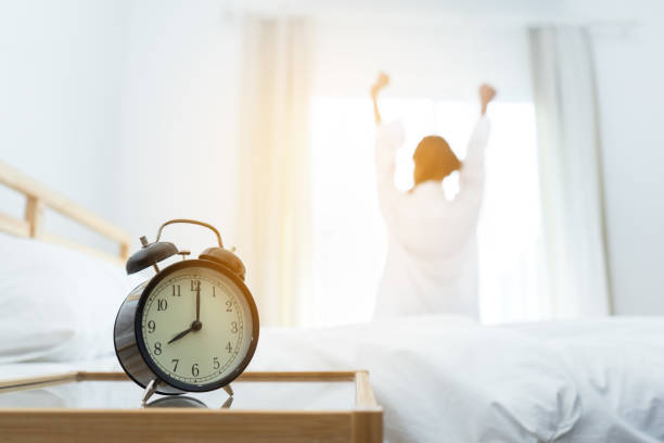 closeup alarm clock, young asian woman wake up in the moring and stiing on bed at mirror door side relaxing in holiday with sunlight - gmail imagens e fotografias de stock
