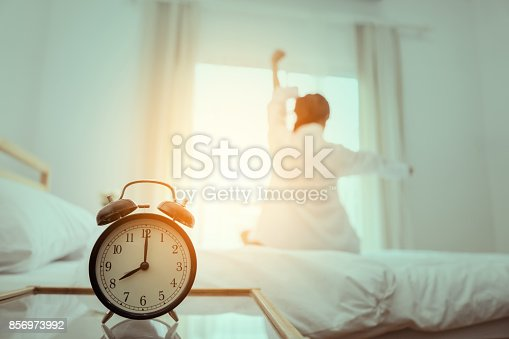 istock Closeup alarm clock, Young asian woman wake up in the morning and sitting on bed at mirror door side relaxing in holiday with sunlight, Vintage 856973992