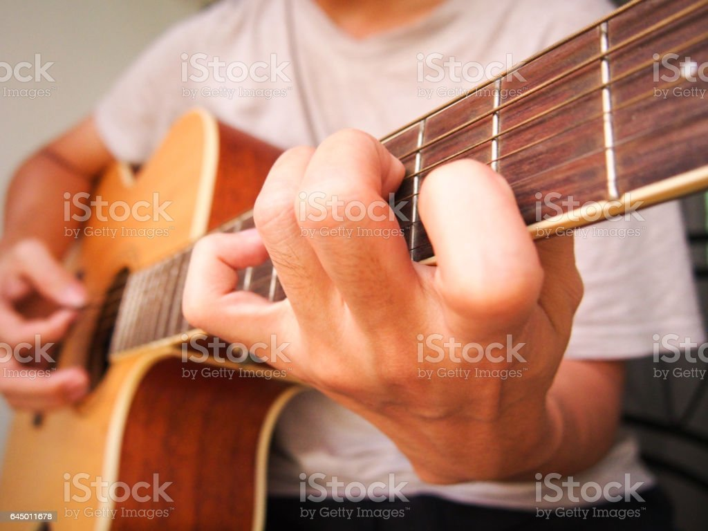 Closeup an acoustic guitar being played stock photo
