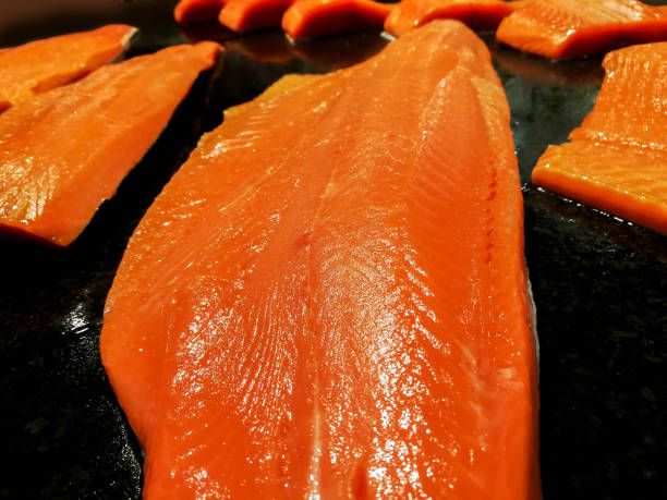 closeup and crop of salmon meat slice for sale on black tray. - chinook salmon stock photos and pictures